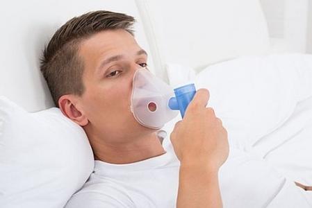 Jeune homme au lit respirant avec un masque d'inhalation